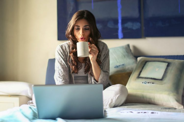 woman in grey jacket sits on bed uses grey laptop 935743 1024x683 1